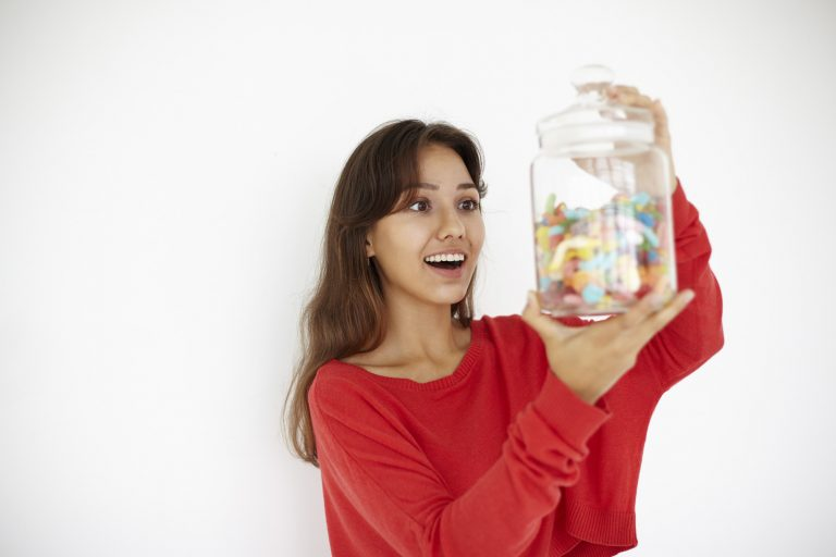 Portrait of excited female holding a jar of gummy candies