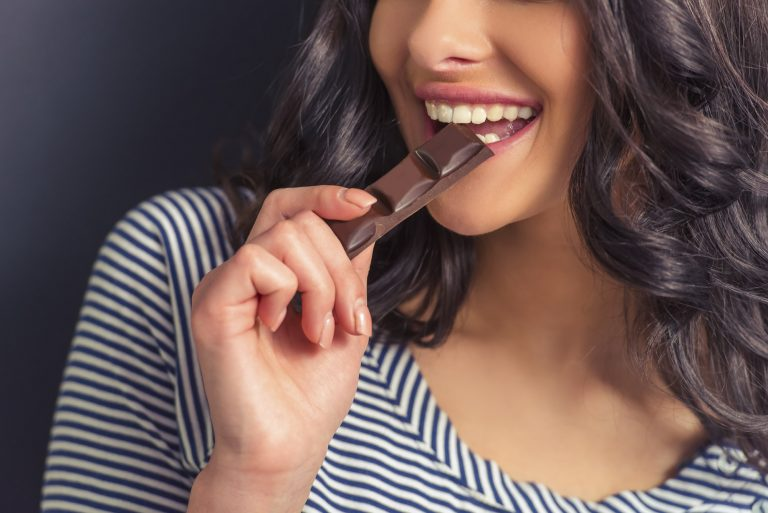 Female eating chocolate and smiling