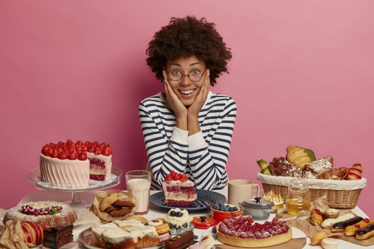 Happy woman behind a table of sugary snacks, including cakes and pies