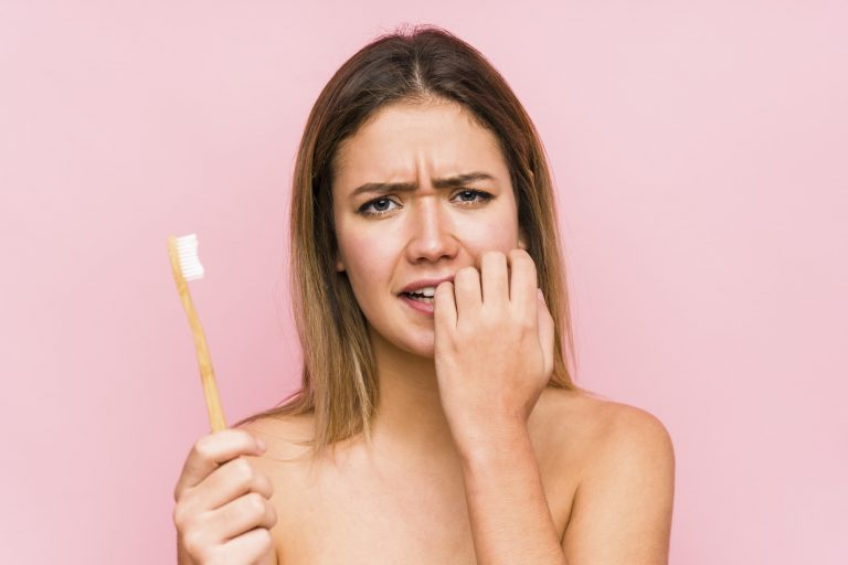 Female with brown hair, appearing stressed, holding a toothbrush in one hand and biting the nails of her other hand