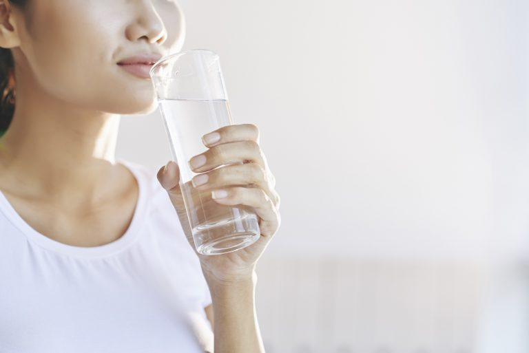 Female holding a glass of water near her mouth