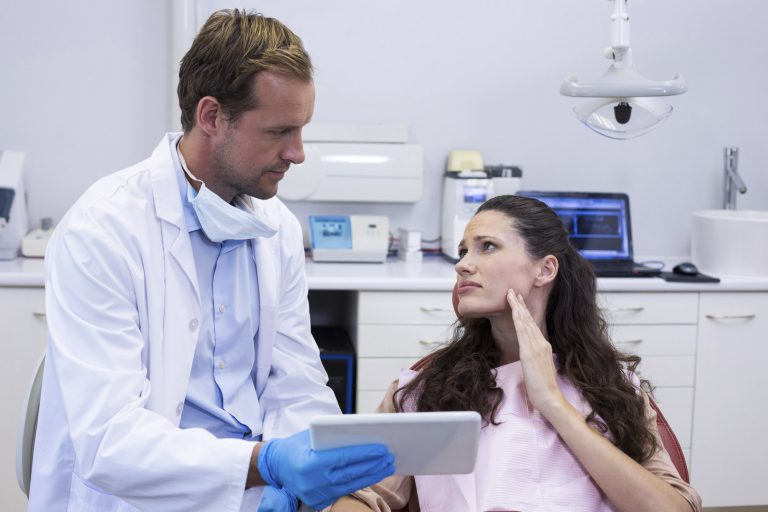 Dentist discussing over digital tablet with female patient in dental clinic