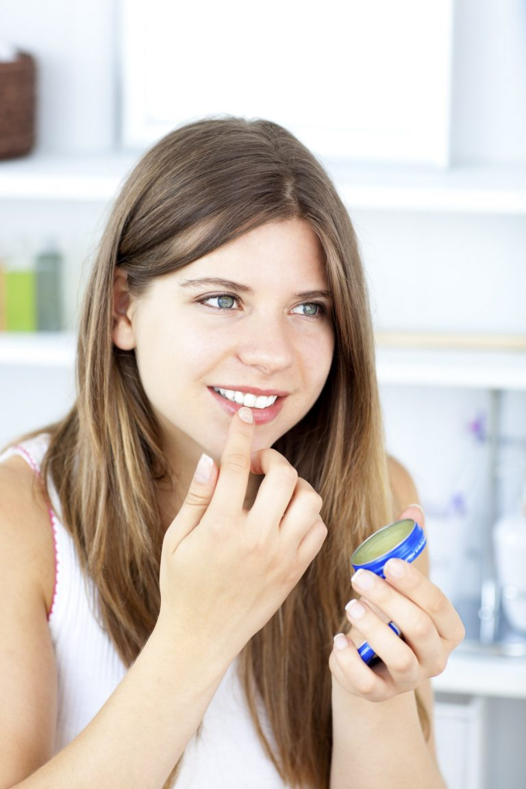 Portrait of woman putting vaseline on her lips