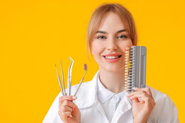 female dentist holds dental tools and a chart with varying colors of teeth