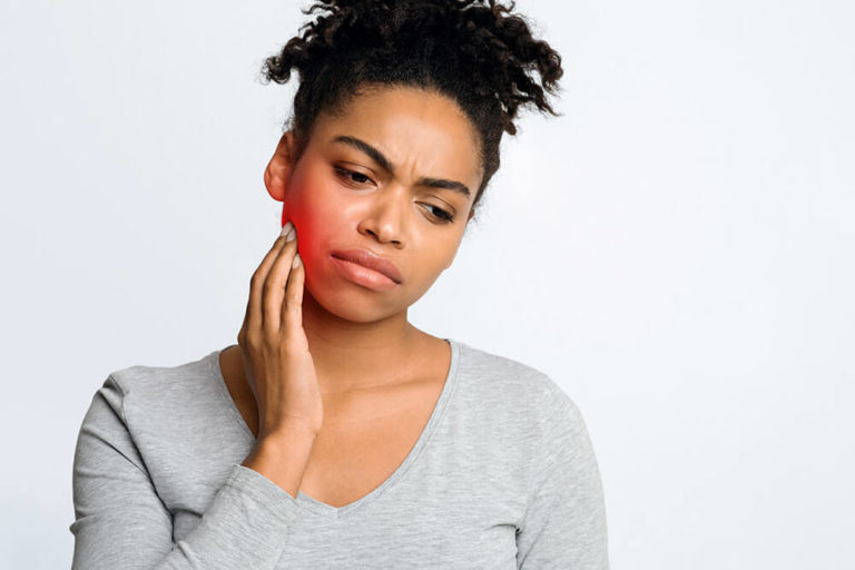 woman holding her cheek, as if she has tooth pain
